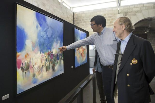 Yvon Chu, fils du peintre, en compagnie de... (Photo: AFP)