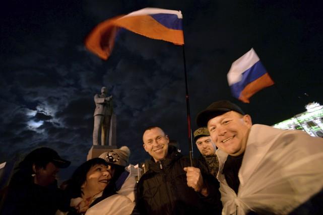 Des Criméens célèbrent le résultat du référendum du... (Archives, Agence France-Presse)