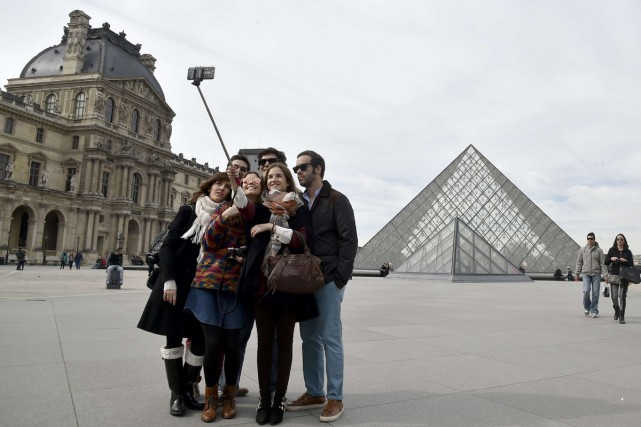 Des touristes utilisent le selfie stick devant le... (Photo: archives AFP)