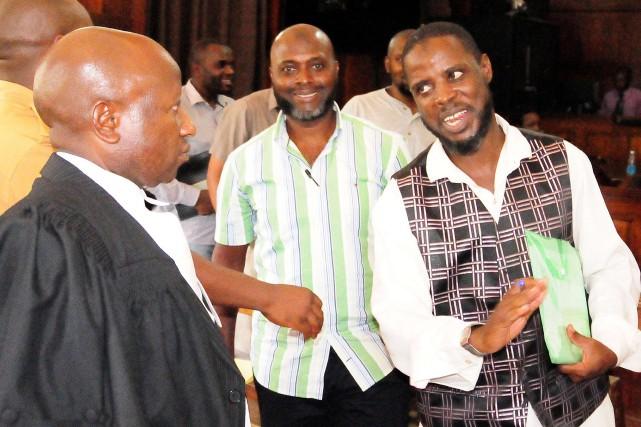 L'un des accusés,Ismail Kasule, parle avec son avocat... (PHOTO PETER BUSOMOKE, AFP)