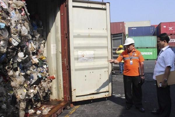 Un superviseur observe un conteneur rempli de déchets... (La Presse Canadienne)