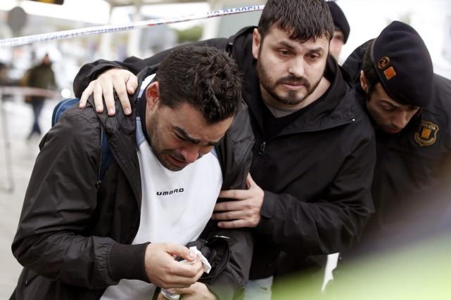 Des membres des familles endeuillées sont pris en... (PHOTO GUSTAU NACARINO, REUTERS)