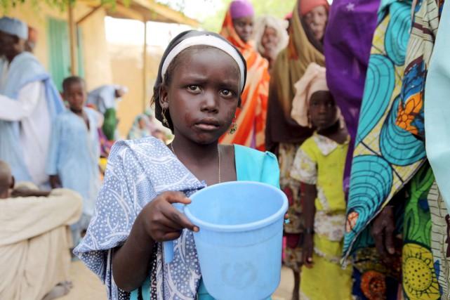 Une jeune fille vient remplir son seau d'eau... (PHOTO JOE PENNEY, REUTERS)