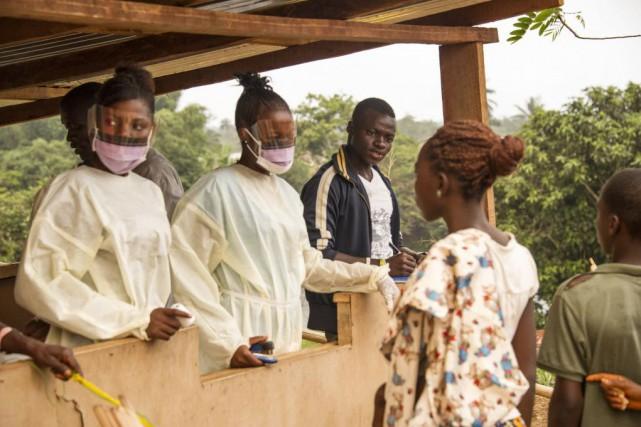 Des travailleurs en santé font des vérifications auprès... (PHOTO ZOOM DOSSO, AFP)