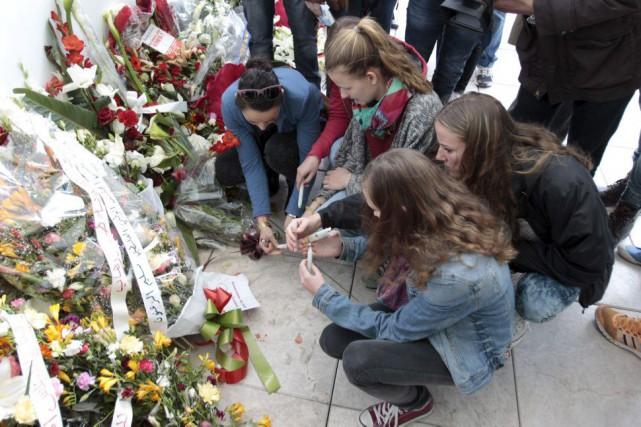 Des touristes déposent des fleurs devant le musée... (PHOTO ZOUBEIR SOUISSI, REUTERS)
