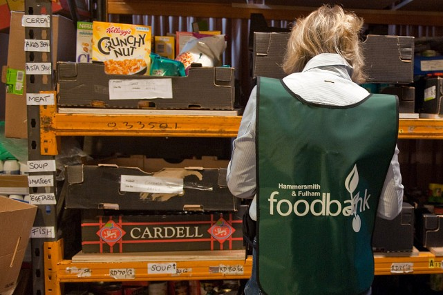 Une employée dans une banque alimentaire triant de... (Archives AFP)