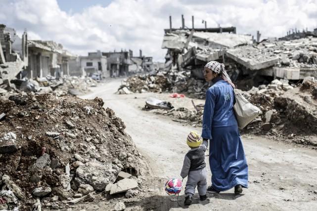 Une femme kurde marche avec son enfant dans... (PHOTO YASIN AKGUL, ARCHIVES AFP)