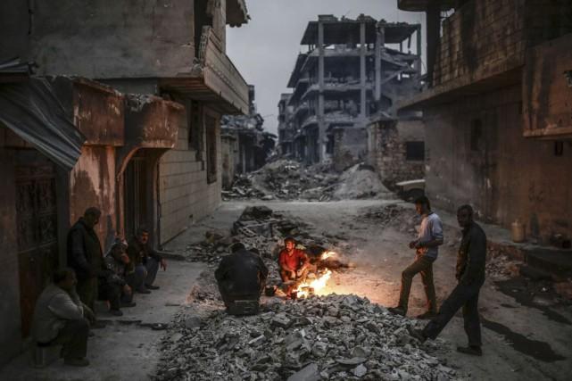 Des Kurdes dans les ruines de Kobané, en... (PHOTO YASIN AKGUL, AFP)