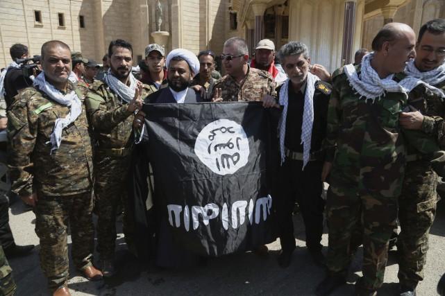 Des membres de Forces de sécurité irakiennes posent... (PHOTO KHALID MOHAMMED, AP)