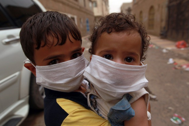 Deux enfants portent un masque pour se protéger... (PHOTO MOHAMMED HUWAIS, AFP)
