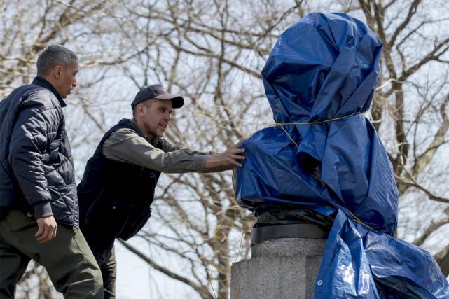 Le buste a d'abord été recouvert de plastique... (PHOTO BRENDAN MCDERMID, REUTERS)