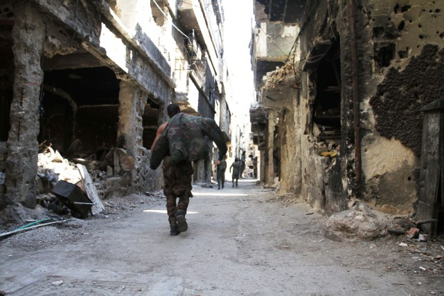 Des combattants marchent dans une rue en ruine... (PHOTO YOUSSEF KARWASHAN, ARCHIVES AFP)