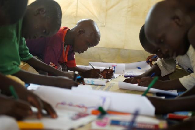 Tous veulent participer à l'atelier de dessin organisé... (PHOTO PHILIPPE DESMAZES, AFP)