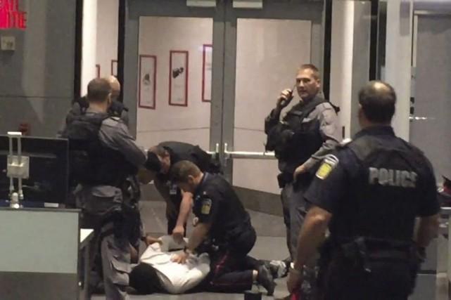 Des policiers maîtrisent un hommequi avait tenté d'entrer... (Photo Vinay Saini, La Presse Canadienne)