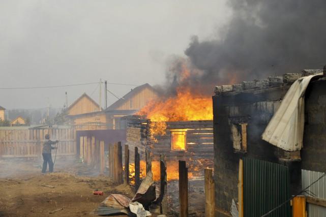 Un homme tente de sauver sa maison des... (PHOTO EVGENY YEPANCHINTSEV, AP)