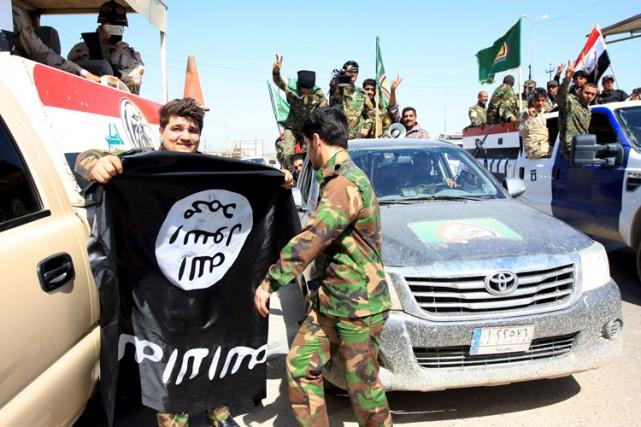 Des combattants irakiens brandissent un drapeau de l'EI,... (Photo: Reuters)