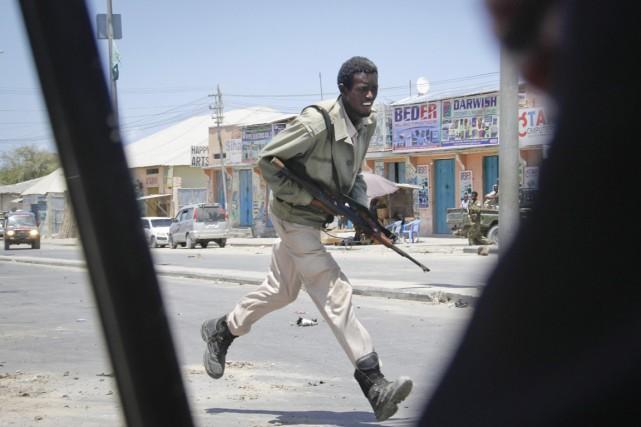 Un soldat somalien court alors que l'attaque des... (PHOTO FARAH ABDI WARSAMEH, AP)