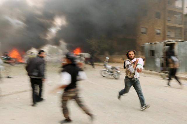 Un homme court, un enfant blessé dans les... (PHOTO AMMAR ABDALLAH, ARCHIVES REUTERS)