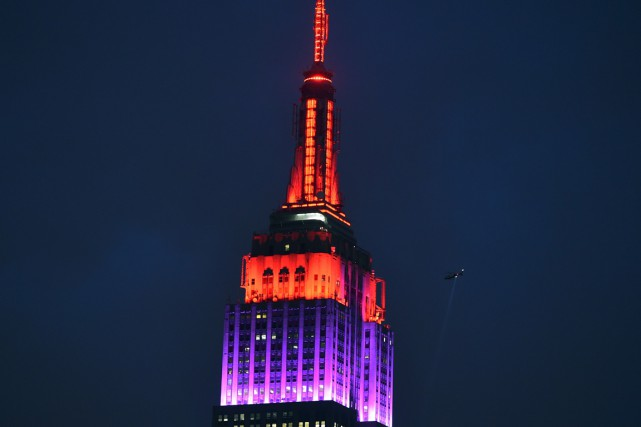 L'Empire State Building à New York s'est illuminé mardi soir de rouge et... (Photo AFP)