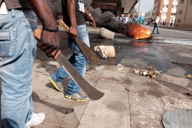 Deux homme sissus de l'immigration marchent dans le... (PHOTO TEBOGO LETSIE, AP)