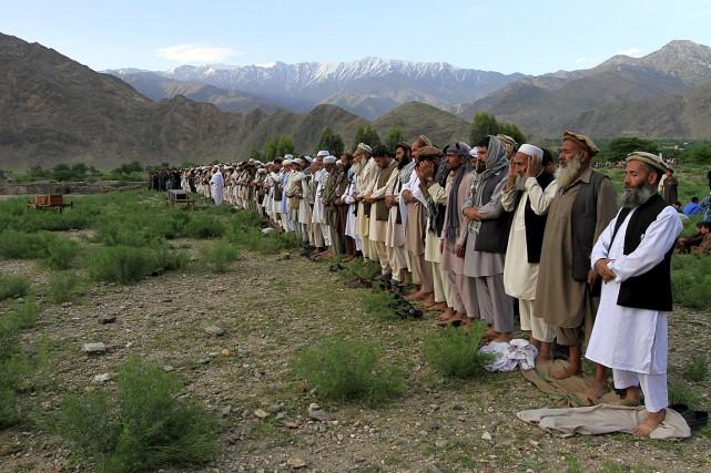 Des gens prient pour la trentaine de victimes... (PHOTO PARWIS, REUTERS)