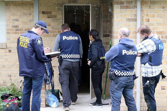 Des policiers perquisitionnent une résidence en banlieue de... (PHOTO HERALD SUN)