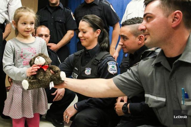 La petite Madeleine Fréchette en compagnie des policiers... (Patrick Woodbury, LeDroit)