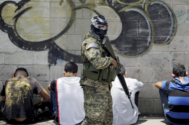 Un militaire salvadorien surveille un groupe de membres... (PHOTO JOSE CABEZAS, REUTERS)