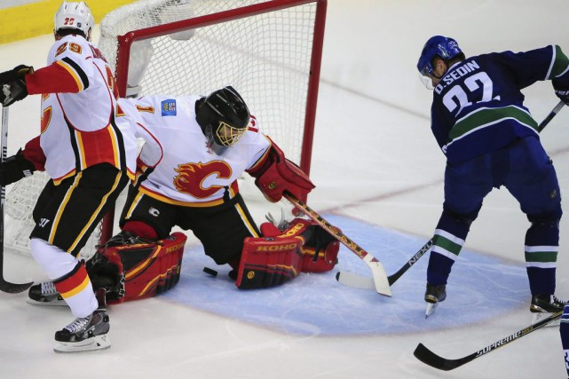 Daniel Sedin (22) marque contre Jonas Hiller (1)... (PHOTO ANNE_MARIE SORVIN, USA TODAY SPORTS)