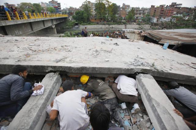 Des secouristes fouillent les débris d'un bâtiment à... (Photo Niranjan Shrestha, AP)