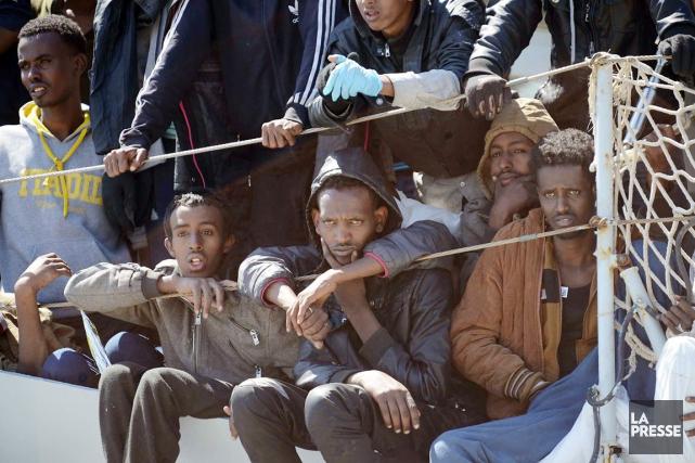 Des migrants attendent de pouvoir débarquer d'un navire... (PHOTO FRANCESCO PECORARO, AP)