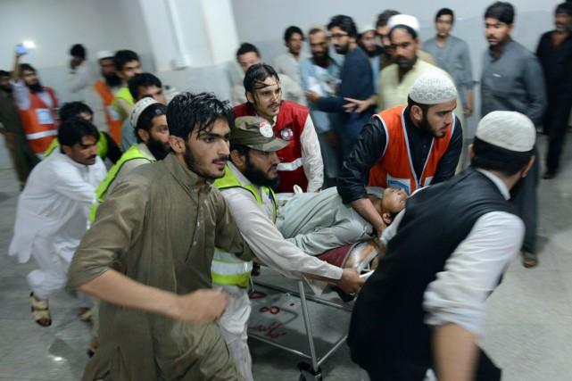 Des hommes aident au transport d'un homme blessé,... (Photo AFP)