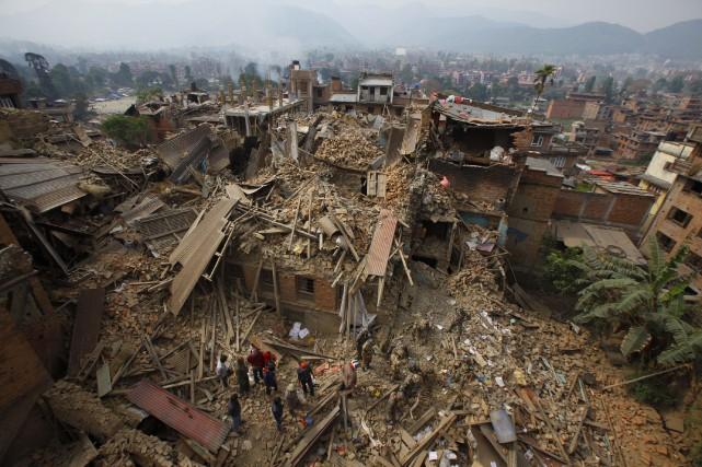 Des secouristes recherchent des survivants dans les décombres.... (Associated Press)