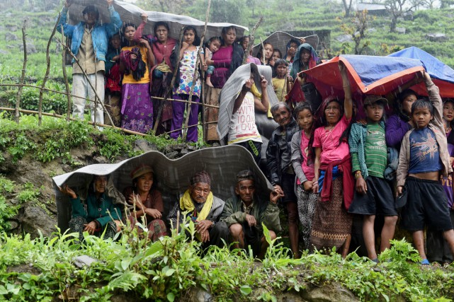 Des villageois ayant vu leurs maisons détruites par... (PHOTO SAJJAD HUSSAIN, AFP)