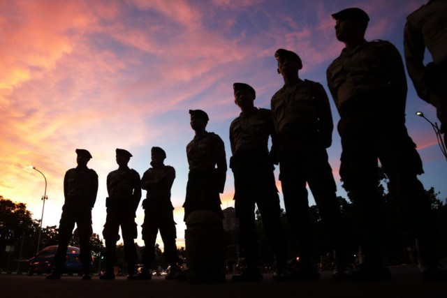 Des gardes surveillent un groupe de manifestants qui... (Photo Achmad Ibrahim, AP)