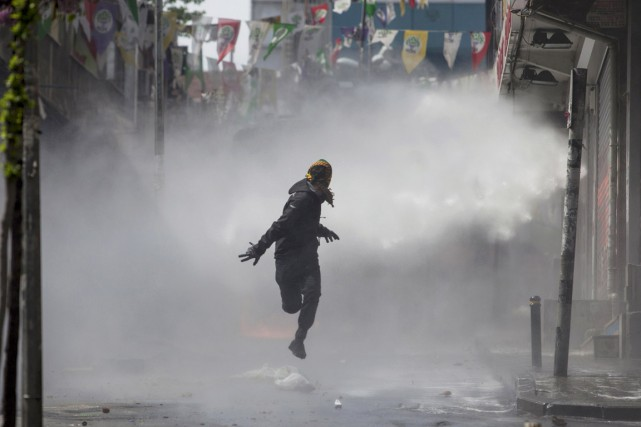 Un manifestant masqué prend ses jambes à son... (PHOTO KEMAL ASLAN, REUTERS)