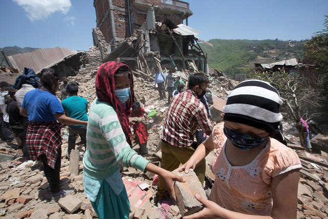 Des Népalais s'entraident au village de Sankhu, dans... (PHOTO MENAHEM KAHANA, AFP)