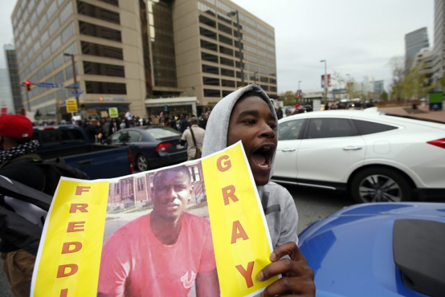 Un homme tient une photo de Freddie Gray... (Photo: AP)