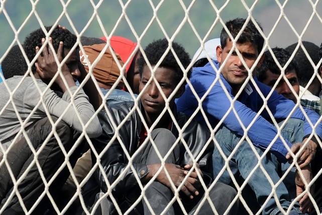 Des migrants ayant traversé la Méditerranée attendent l'autorisation... (PHOTO FRANCESCO PECORARO, AP)