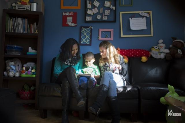 Julian et sa mère Dileni regardent un livre... (Photo Olivier Pontbriand, La Presse)