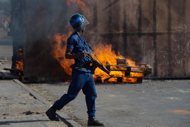 Un policier passe devant une barricade en feu... (PHOTO PHIL MOORE, ARCHIVES AFP)