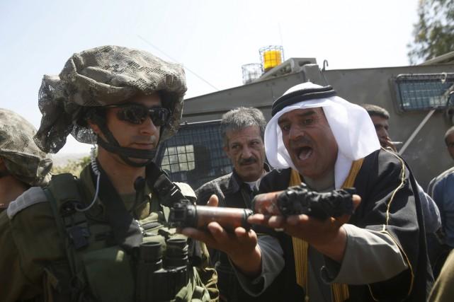 Un Palestinien montre à un soldat israélien des... (PHOTO MUSSA QAWASMA, REUTERS)