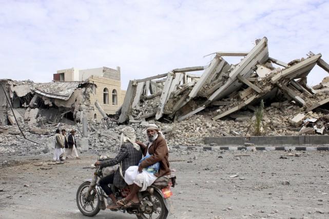 Deux Yéménites passent à moto devant les ruines... (PHOTO KHALED ABDULLAH, AFP)