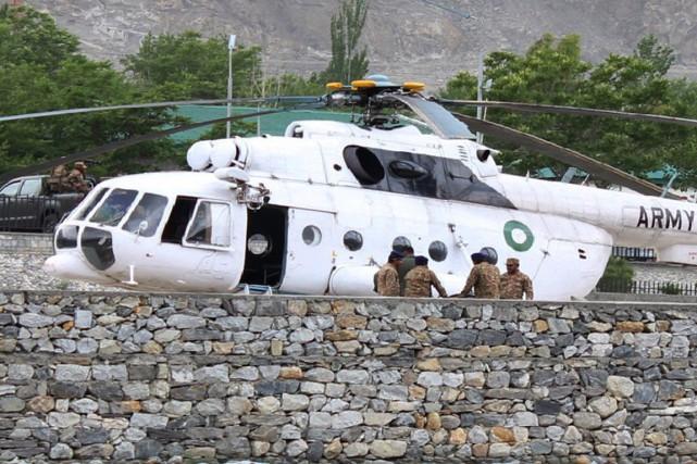 Des soldats pakistanais discutent devant un hélicoptère sur... (PHOTO FARMAN KARIM, AFP)
