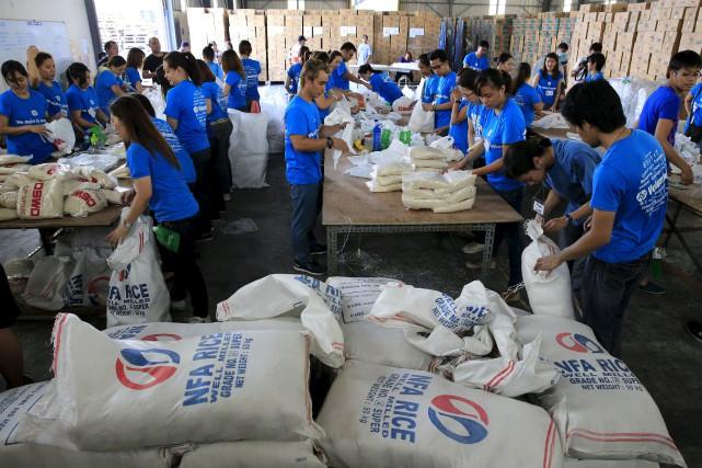 Des bénévoles préparent des sacs de nourritures en... (Photo Romeo Ranoco, Reuters)