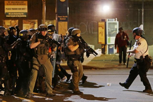 Des policiers anti-émeutes retraitent après avoir arrêté un... (PHOTO DAVID GOLDMAN, ARCHIVES AP)