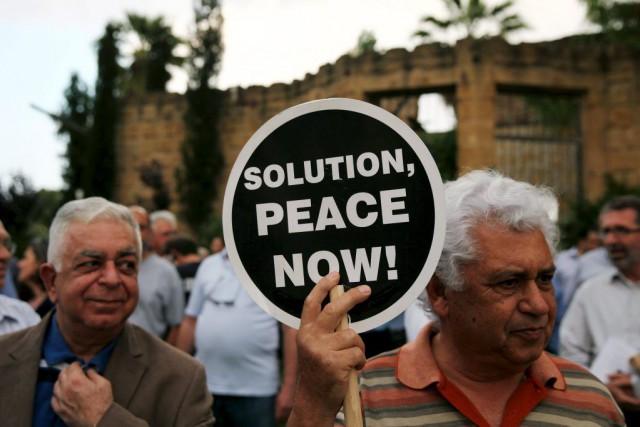 Un homme tient une pancarte demandant la paix... (PHOTO YIANNIS KOURTOGLOU, REUTERS)