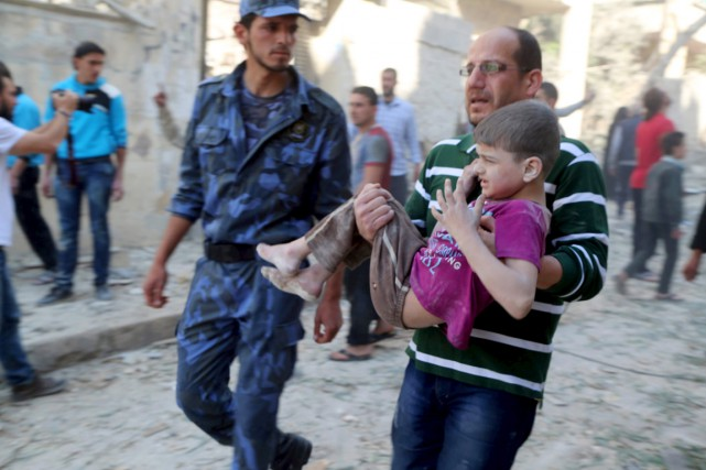 Un homme transporte un garçon blessé à la... (PHOTO HOSAM KATAN, ARCHIVES REUTERS)