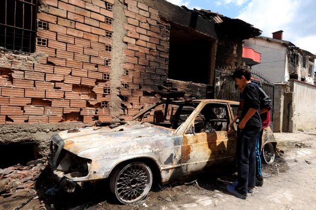 Deux jeunes garçons regardent une voiture incendiée lors... (PHOTO ROBERT ATANASOVSKI, ARCHIVES AFP)