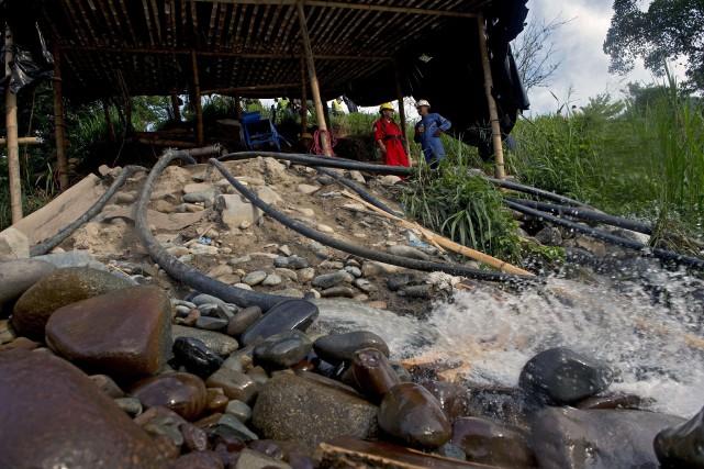 Les secouristes pompent l'eau pour tenter d'atteindre les... (PHOTO  LUIS ROBAYO, AFP)